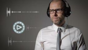 O homem de negócios em uma camisa e em uns fones de ouvido grandes, clica sobre o botão do jogo e começa-o escutar a música video estoque