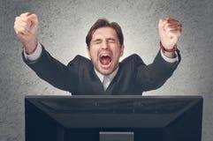 O homem de negócios emocional exulta a vitória no computador Fotos de Stock
