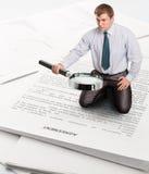 O homem de negócios encontra algo com lupa Foto de Stock Royalty Free