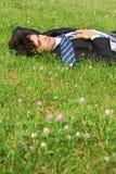 O homem de negócios encontra-se sobre para trás na grama com olhos fechados imagem de stock