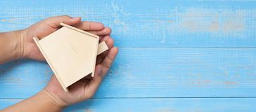 O homem de negócios entrega guardar o modelo de madeira da casa na tabela azul da madeira da cor pastel imagem de stock royalty free