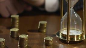 O homem de negócios entrega os sandglass de giro, pilhas das moedas na tabela, período do investimento filme