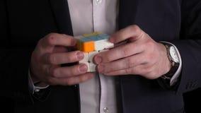 O homem de negócios entrega a resolução do enigma do cubo do ` s de Rubik em um fundo preto vídeos de arquivo