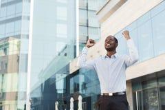 O homem de negócios entusiasmado feliz comemora Vencedor, homem negro fora imagens de stock