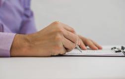 O homem de negócios escreve em um caderno ao sentar-se em uma mesa Fotografia de Stock