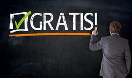 O homem de negócios escreve gratuitamente no alemão gratuitamente no blackboa imagens de stock royalty free