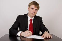 O homem de negócios escreve no papel Foto de Stock