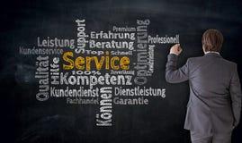 O homem de negócios escreve o serviço na competência alemão, consultando o cl imagem de stock royalty free