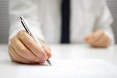 O homem de negócios está assinando o contrato fotografia de stock royalty free