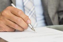 O homem de negócios está assinando um contrato, foco na pena Imagens de Stock Royalty Free