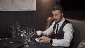 O homem de negócios está bebendo o chá preto vídeos de arquivo