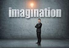 O homem de negócios está com palavra grande 'da imaginação 3d' acima Foto de Stock Royalty Free