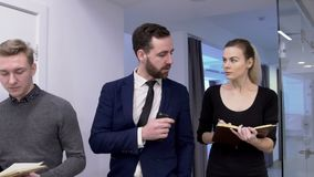 O homem de negócios está dando tarefas a seu homem e a fêmea interna no escritório filme