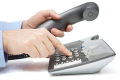 O homem de negócios está discando o número de telefone com monofone à disposição imagem de stock royalty free
