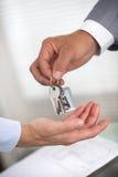 O homem de negócios está entregando uma chave da casa a um homem da casa nova Fotografia de Stock Royalty Free