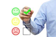 O homem de negócios está escolhendo o sorriso na lista de verificação imagem de stock