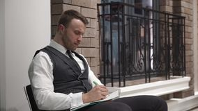 O homem de negócios está escrevendo algo em seu diário filme