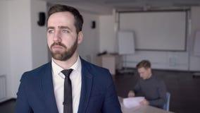 O homem de negócios está estando em seu escritório e está esperando o colega filme