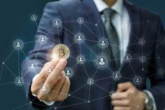 O homem de negócios está guardando um bitcoin como parte de uma rede do negócio Fotos de Stock