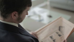 O homem de negócios está lendo o jornal no salão da sala de estar do vip no aeroporto filme