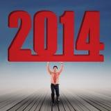 O homem de negócios está levantando o ano novo 2014 exterior Foto de Stock
