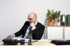 O homem de negócios está pensando, quando se dobrar sobre um dobrador imagem de stock