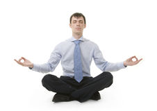 O homem de negócios está sentando-se na posição da ioga imagens de stock