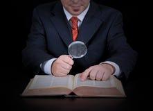 O homem de negócios está usando a lupa Foto de Stock Royalty Free