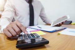 O homem de negócios está usando uma calculadora para calcular os números fotografia de stock royalty free