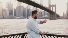 O homem de negócios europeu feliz está pela cerca da terraplenagem do rio na ponte de Brooklyn New York, olhando o relógio espert vídeos de arquivo