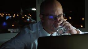 O homem de negócios executivo trabalha no caderno e bebe a água no escritório da noite filme