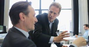 O homem de negócios explica a ideia ao colega de trabalho que aponta no monitor do computador no escritório moderno, executivos b video estoque