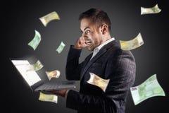 O homem de negócios exulta no voo do dinheiro de um portátil Salário em linha do conceito, jogo, autônomo fotografia de stock royalty free