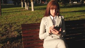O homem de negócios fêmea está vestindo vidros e está trabalhando com tabuleta e está verificando o email no parque do verão em u video estoque