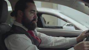 O homem de negócios farpado bem sucedido atrativo do retrato que senta-se no veículo e inspeciona comprou recentemente auto do ca filme
