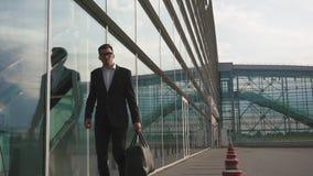 O homem de negócios farpado elegante ajusta seu revestimento antes que curso do trabalho filme