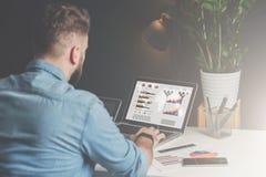 O homem de negócios farpado novo está sentando-se no escritório na tabela e está usando-se o portátil com cartas, gráficos e diag Fotos de Stock