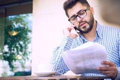 O homem de negócios farpado novo na roupa ocasional e nos monóculos está estudando o documento ao falar no assento do smartphone fotografia de stock
