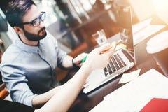O homem de negócios farpado novo nos vidros analisa os trabalhos de equipa feitos Imagem de Stock Royalty Free