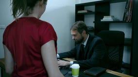 O homem de negócios farpado que senta-se no escritório no portátil, menina no vermelho está tentando seduzir o chefe, movimento l video estoque