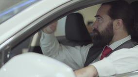 O homem de negócios farpado seguro atrativo do retrato que senta-se no veículo e inspeciona comprou recentemente auto do carro vídeos de arquivo