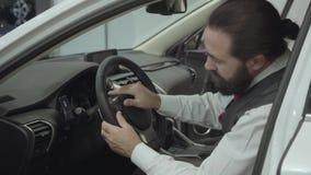 O homem de negócios farpado seguro atrativo do retrato que senta-se no veículo e inspeciona comprou recentemente auto do carro video estoque
