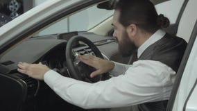 O homem de negócios farpado seguro atrativo do retrato que senta-se no veículo e inspeciona comprou recentemente auto do carro filme