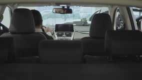 O homem de negócios farpado seguro atrativo do retrato senta-se no veículo e inspeciona-se comprou recentemente auto do carro video estoque