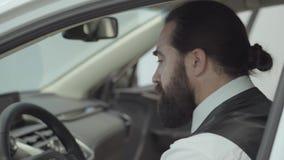 O homem de negócios farpado seguro bonito atrativo do retrato que senta-se no veículo e inspeciona comprou recentemente auto do video estoque