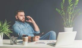 O homem de negócios farpado senta-se no escritório na tabela, inclinando-se para trás na cadeira e falando no telefone celular ao Imagens de Stock Royalty Free