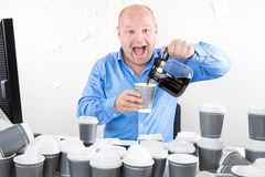 O homem de negócios feliz bebe demasiado café Imagens de Stock Royalty Free
