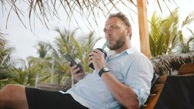 O homem de negócios feliz bem sucedido aprecia a bebida na cadeira de sala de estar na praia do verão, pensando, usando o app do  filme