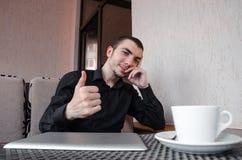 O homem de negócios feliz com tabuleta digital faz um polegar do gesto acima no café e na xícara de café da bebida Foto de Stock Royalty Free