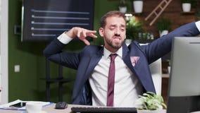 O homem de negócios feliz começa dançar em sua mesa filme